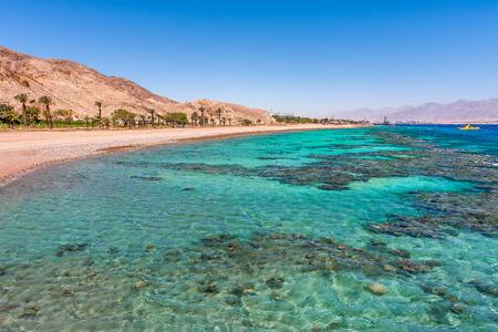 Aquamarine agua y los corales bajo el agua a lo largo de la playa vacía en popular balneario de Eilat en el Mar Rojo en Israel