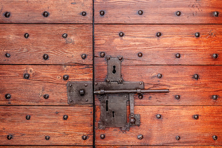 Old red wooden door with metal lock and bolt  photo