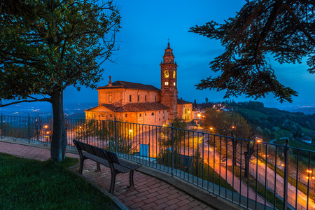 Bench on walkway and view of illuminated church on background in the morning in Piedmont, Northern Italy  photo