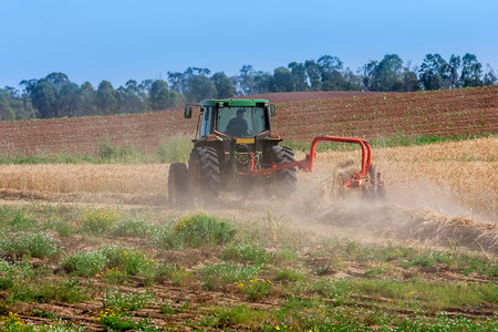 Tractor plow the soil on agricultural field in the clowds of dust at hot spring day  photo