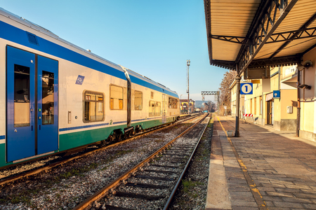 Contemporary suburban train on rails and empty platform of roailroad station in Alba, Italy  Stock Photo