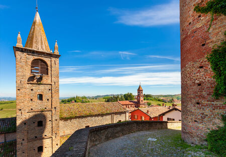 Bell tower and medieval brick wall under blue sky in small town of Serralunga D Stock Photo - 29237625