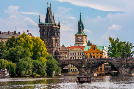Medieval tower and famous Charles Bridge over Vltava river in Prague, Czech Republic