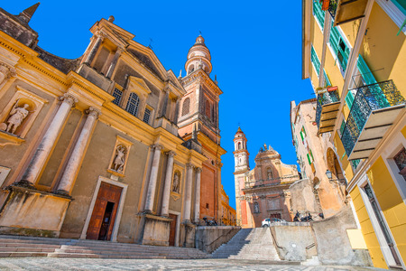 azur: Basilica of Saint Michael Archange on small town square under blue sky in Menton, France