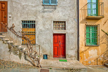 saluzzo: Facade of typical italian house with colorful windows and doors in town of Saluzzo in Piedmont, Northern Italy