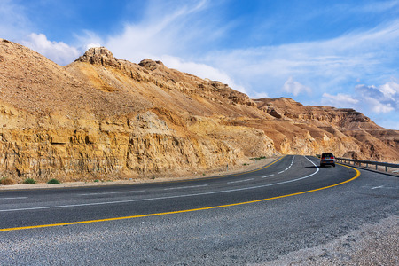 arava: Highway along mountains of Arava desert under beautiful cloudy sky in Israel
