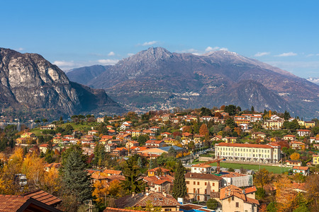 lake como: View of small town surrounded by mountains on the shores of Lake Como in autumn in Italy. Stock Photo