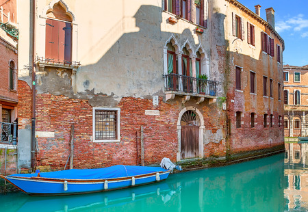 small boat: Boat on narrow canal among old brick houses in Venice, Italy.