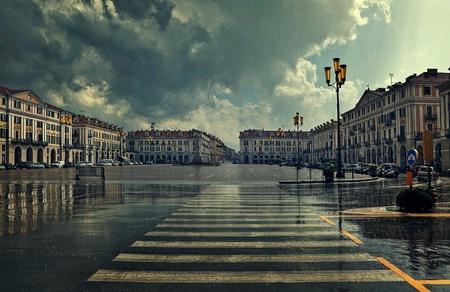 paso de peatones: Paso de peatones y gran plaza en el centro de la ciudad bajo el cielo nublado en el día lluvioso en Cuneo, Italia.