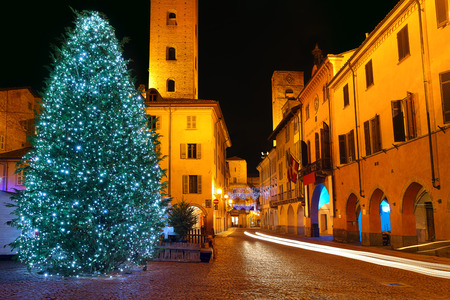 Illuminated Christmas tree on city central square in town of Alba, Italy.