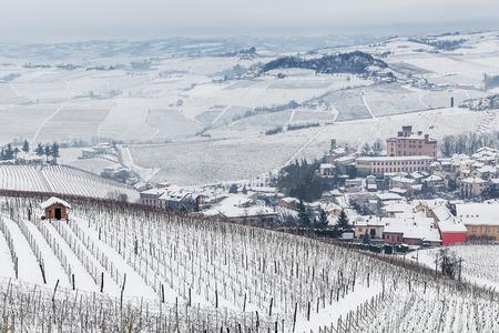 vi�edo: ciudad centro comercial de Barolo y vi�edos en las colinas cubiertas de nieve en el Piamonte, norte de Italia. Foto de archivo
