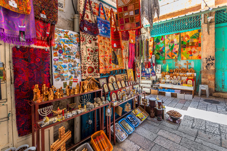 JERUSALEM, ISRAEL - JULY 10, 2014: Stands with colorful oriental carpets and variety of religious icons and gifts at bazaar - famous market place popular with tourists and pilgrims in Old City of Jerusalem.
