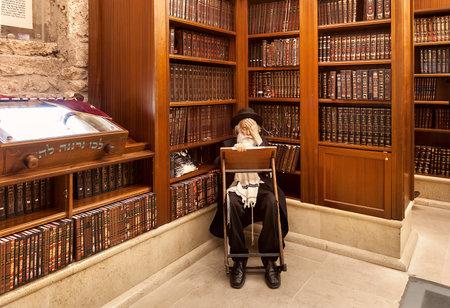 エルサレム, イスラエル - 2014 年 7 月 10 日: 古いラビは洞窟のシナゴーグの神聖な本を木製の本棚の中で律法を学ぶ - エルサレムで有名な国島壁の一部であるユダヤ教の古い神聖な場所します。 写真素材 - 39008918
