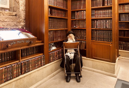 JERUSALEM, ISRAEL - JULY 10, 2014: Old rabbi learns Torah among wooden bookshelves with holy books in Cave Synagogue - old sacred place for Judaism which is part of famous Wastern Wall in Jerusalem. 에디토리얼