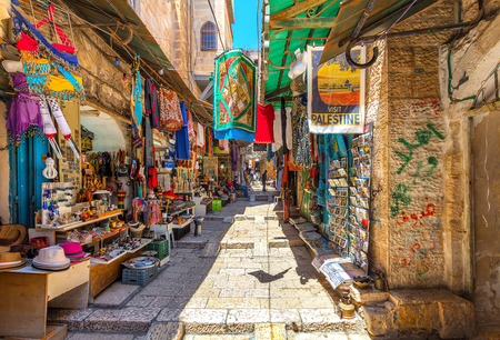 traditional goods: JERUSALEM, ISRAEL - JULY 10, 2014: Narrow stone street among stalls with traditional souvenirs and goods at bazaar in Old City - popular place among tourists and pilgrims visiting Jerusalem. Editorial