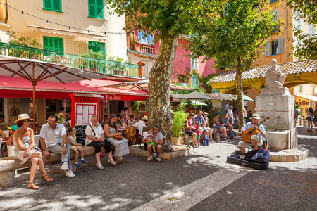 french cafe: MENTON, FRANCE - AUGUST15, 2014: People listening to street musician on small square in old town of Menton - popular tourist resort on French Riviera, famous for its gardens and annual Lemon Festival taking place every February.