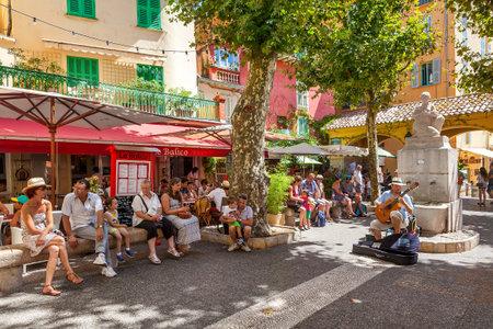 MENTON, FRANCE - 15 Août 2014: Les gens l'écoute de musicien de rue sur la petite place de la vieille ville de Menton - station touristique populaire de Côte d'Azur, célèbre pour ses jardins et annuelle Fête du Citron qui a lieu chaque Février.