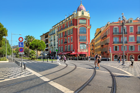traditional celebrations: NICE, FRANCE - SEPTEMBER 12, 2014: Tramway rails and colorful buildings on Place Massena - one of the main city squares, place for concerts, parades, carnivals, traditional celebrations and other public events.