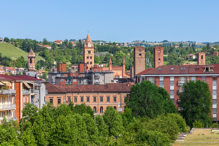 Medieval towers and belfries among modern buildings and green trees in town of Alba in Piedmont Northern Italy.