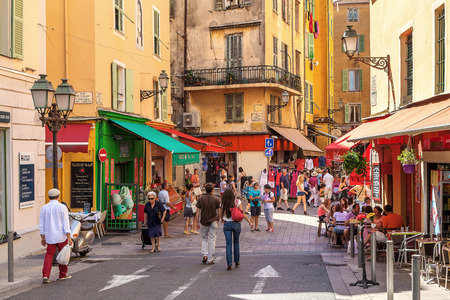 NICE FRANCE  AUGUST 23 2014: Tourists sitting in outdoor restaurants and walking in Old City of Nice  fifth most populous and secondlargest French city on Mediterranean coast and one of the most visited receiving 4 million tourists every year.