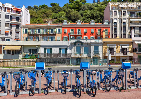nice france: City bicycles at sharing station and colorful houses on background in city of Nice, France.