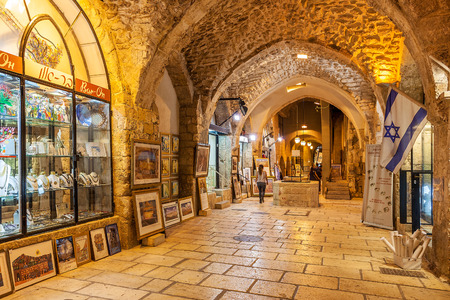 souvenir: JERUSALEM, ISRAEL - JULY16, 2015: Gift shops  gallery in ancient stone vault passage in Old City of Jerusalem - one of the oldest cities in the world and holy in Judaism, Islam and Christianity.