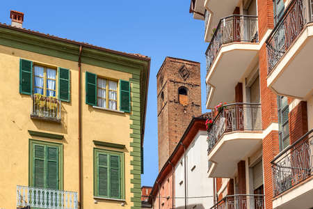 town houses: Medieval tower among typical italian houses in town of Alba in Piedmont, Northern Italy.