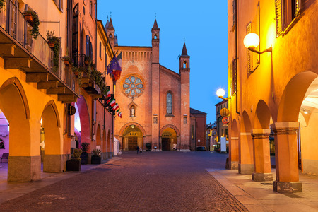 Buildings, narrow cobblestone street and cathedral on background in old town of Alba in evening in Piedmont, Northern Italy. Standard-Bild