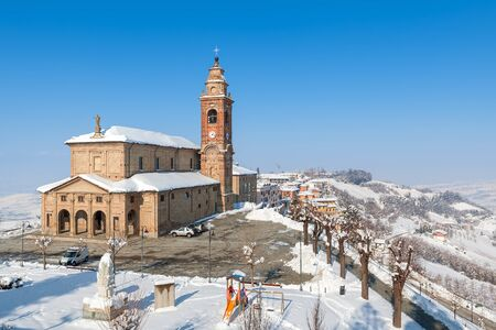 europe travel: View on parish church and snowy hills of Piedmont, Northern Italy.
