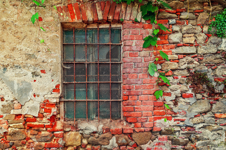 old town house: Fragment of old abandoned brick house with closed window behind iron bars in small italian town in Piedmont, Northern Italy. Stock Photo