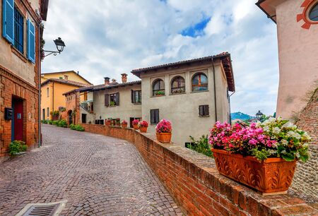 ow cobblestone street among old houses in town of Barolo in Piedmont, Northern Italy.