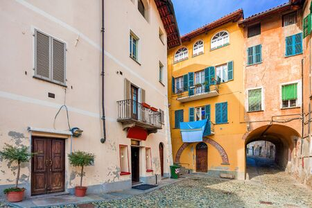 saluzzo: Small backstreet among between colorful houses in town of Saluzzo in Piedmont, Northern Italy. Stock Photo