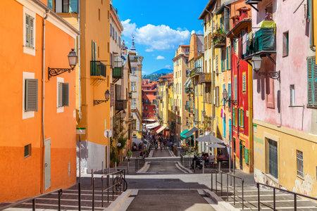 NICE, FRANCJA - 23 sierpnia 2014: Wąska ulica w starej części turystycznej w Nicei - najbardziej piąte miasto i jedno z najczęściej odwiedzanych miast we Francji, które każdego roku otrzymuje 4 miliony turystów.