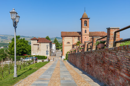 cavour: Brick wall along cobblestone walkway and parish church on background under blue sky in Piedmont, Northern Italy.
