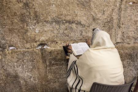 JERUSALEM, ISRAEL - JULY 16, 2015: Prayer prays at Western Wall on Tisha BAv - annual fast day in Judaism, commemorates anniversary of number of disasters in Jewish history and destruction of the First and Second Temples in Jerusalem. Editorial