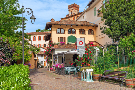 Narrow street among houses with flowers in town of Barolo in Piedmont, Northern Italy.