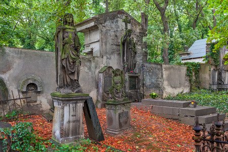 PRAGUE, CZECH REPUBLIC - SEPTEMBER 23, 2015: Statues and graves on old Olšany Cemeteries - largest graveyard in Prague with almost 2 million burials, created in 1680 and noted for its remarkable monuments.