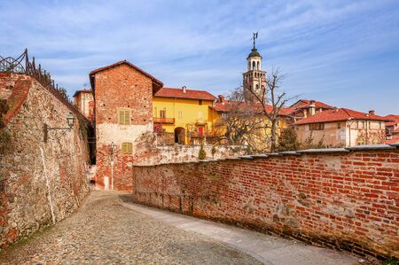 saluzzo: Cobbled street, red brick wall and colorful houses in old town of Saluzzo in Piedmont, Northern Italy. Stock Photo