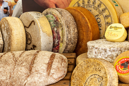BRA, ITALY - SEPTEMBER 18, 2015: Different types of mature hard cheese on the stand. Hard cheese (granular cheese) produced by stirring and draining mixture of curd and whey and has rich tangy taste. Editorial