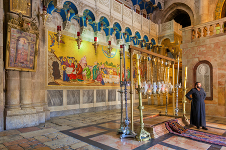 designate: JERUSALEM, ISRAEL - JULY 26, 2015:  Stone of Anointing and mosaic icon on the wall at the entrance to Holy Sepulcher church designate the place where Jesus body was prepared for burial.