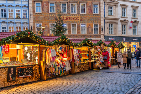 czech: PRAGUE, CZECH REPUBLIC - DECEMBER 10, 2015: Wooden booths in Old Town offering souvenirs and products during traditional Christmas market taking place each year on December. It is very popular destination with tourists visiting Prague.
