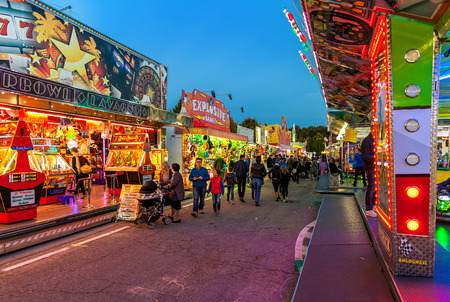 ALBA, ITALY - OCTOBER 10, 2015: People walking by illuminated stalls and attraction at Luna Park - traditional amusement park taking place each year on october during International White Truffle Festival in Alba, Italy.