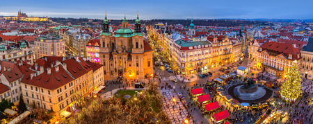 PRAGUE, CZECH REPUBLIC - DECEMBER 10, 2015: Panoramic view from above of city skyline, illuminated buildings and traditional Christmas market on Old Town Square in Prague - famous and popular destionation with locals and tourists during winter holidays.