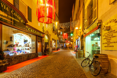 truffe blanche: ALBA, ITALY - DECEMBER 22, 2014: Shops and cobbled pedestian street illuminated and decorated for Christmas holidays in Alba - town in Piedmont, capital of hilly area of Langhe, famous for white truffle, peach and wine production.