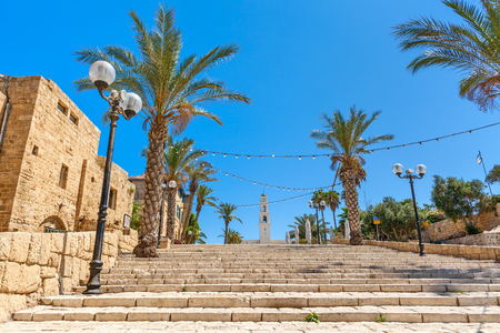 yafo: Lampposts and palms along stone stairs under blue sky in old town of Jaffa, Israel.