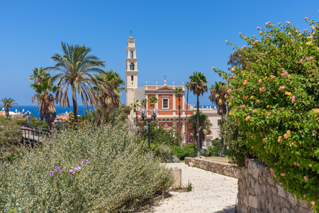 yaffo: View of Saint Peters church among green trees, palms and bushes under blue sky in old jaffa, Israel. Stock Photo