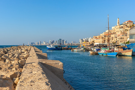 yafo: View from breakwater on small port with boats, old Jaffa and Tel Aviv on background under blue sky in Israel.