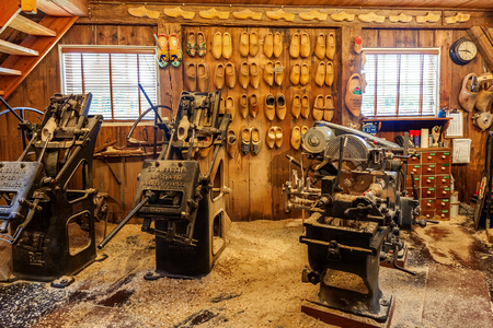 klompen: ZAANSE SCHANS, NETHERLANDS - JULY 08, 2015: Vintage machine tools in small workshop in Zaanse Schans producing klompen (clogs) - famous traditional dutch footwear made completely from wood. Editorial