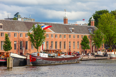 Old boat on canal in front of red brick building in Amsterdam, Netherlands.