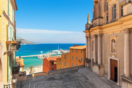 menton: Small town square between old church and colorful houses with view on Mediterranean sea in Menton, France.